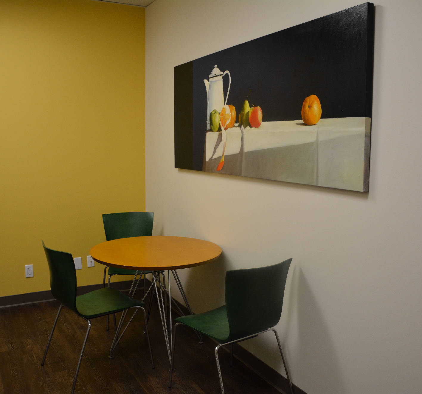 This Is A Pleasant Eating Space With A Table And 3 Chairs Designed With The  Orange And Green Of Art In Mind.